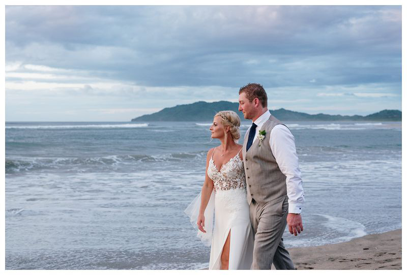 Bride and groom walking on the beach. Destination tropical wedding in Tamarindo, Costa Rica. Photographed by Kristen M. Brown, Samba to the Sea Photography.