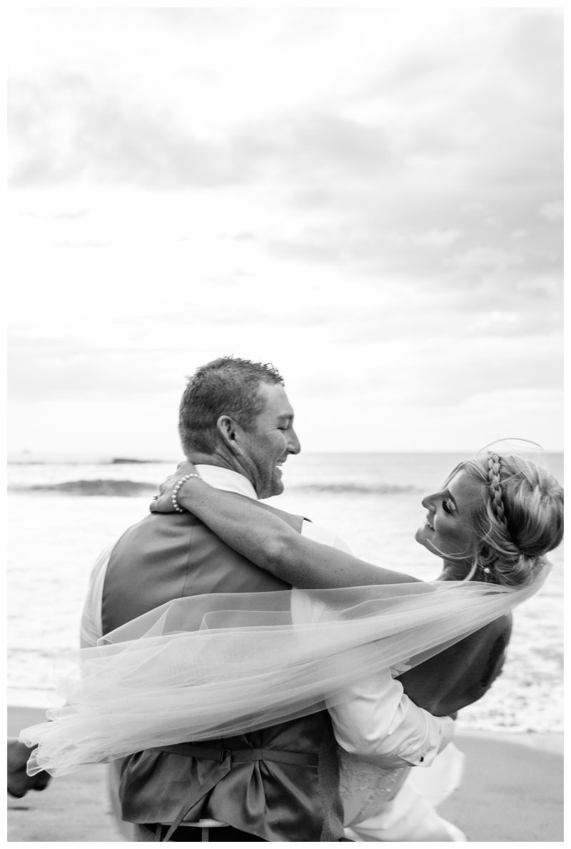 Groom carrying his bride on the beach. Destination tropical wedding in Tamarindo, Costa Rica. Photographed by Kristen M. Brown, Samba to the Sea Photography.