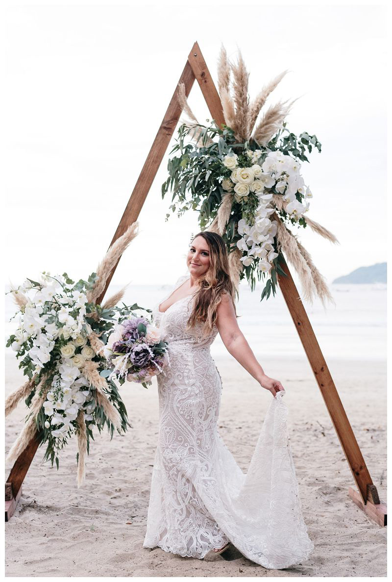 Bridal portrait in front of pampas grass wood altar. Intimate beach wedding in Tamarindo Costa Rica. Photographed by Kristen M. Brown, Samba to the Sea Photography.
