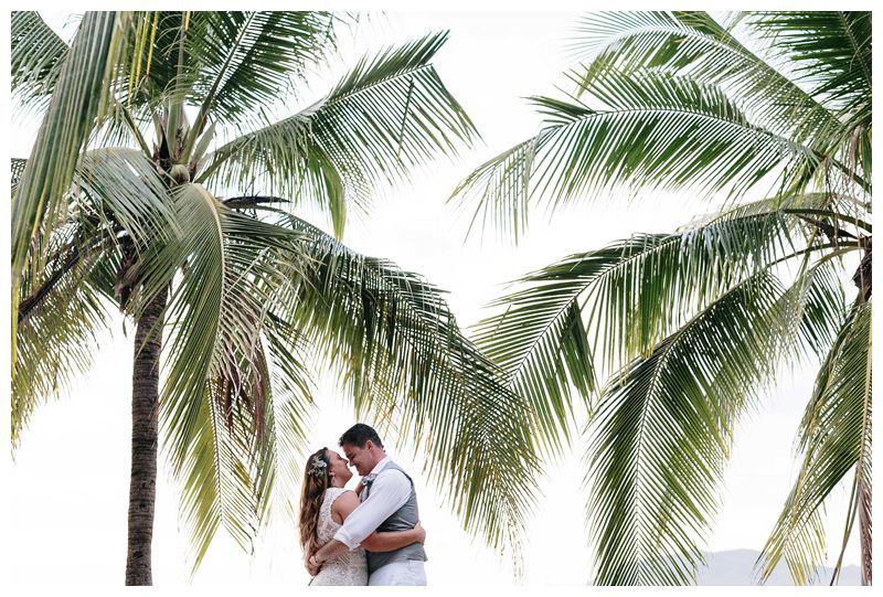 Bride and groom kissing under palm trees. Intimate beach wedding in Tamarindo Costa Rica. Photographed by Kristen M. Brown, Samba to the Sea Photography.