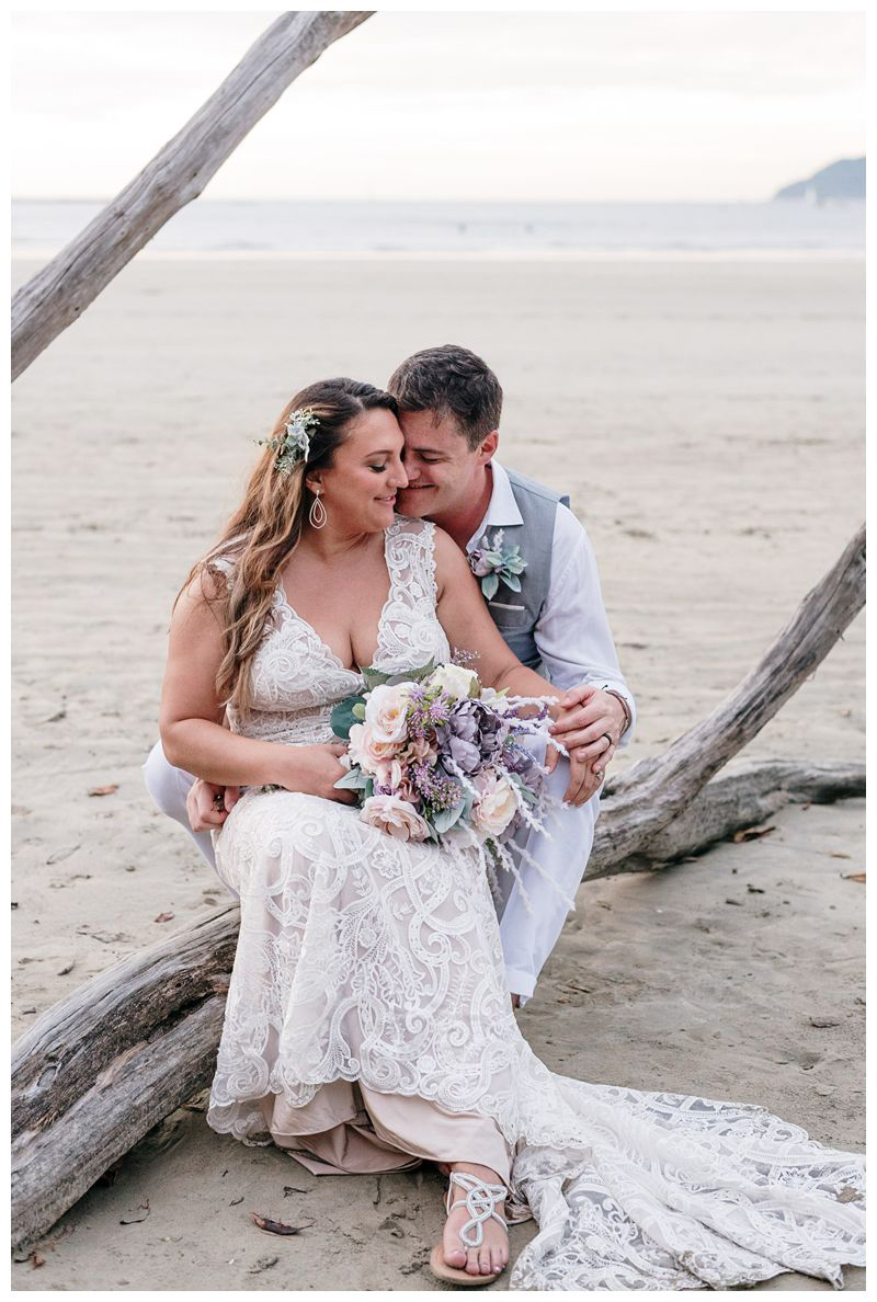 Bride and groom sitting on a piece of driftwood. Intimate beach wedding in Tamarindo Costa Rica. Photographed by Kristen M. Brown, Samba to the Sea Photography.