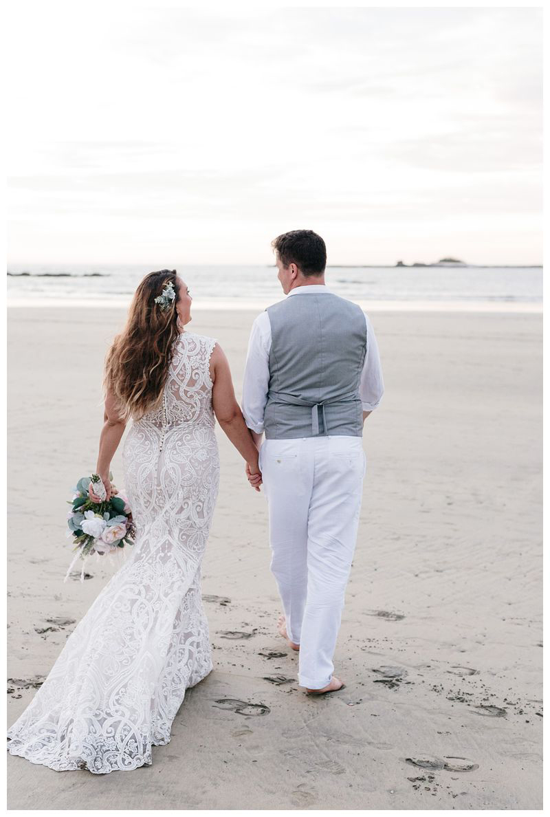 Bride and groom walking on the beach. Intimate beach wedding in Tamarindo Costa Rica. Photographed by Kristen M. Brown, Samba to the Sea Photography.