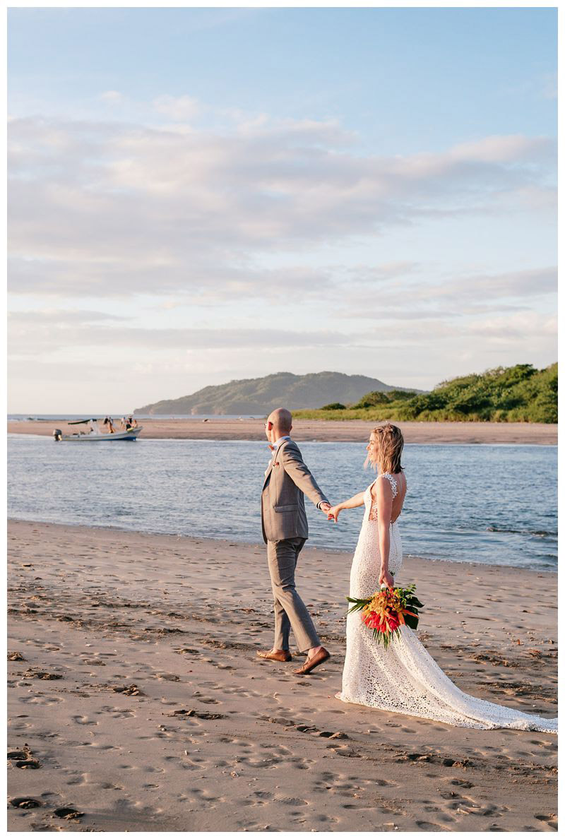 Bride and groom walking on the beach. Intimate destination beach wedding in Tamarindo Costa Rica. Photographed by Kristen M. Brown, Samba to the Sea Photography.