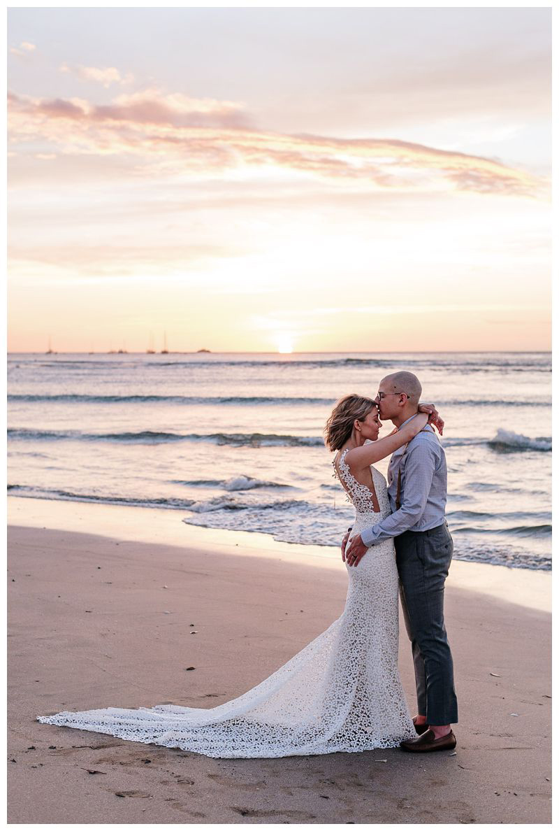 Groom kissing bride on the beach during a beautiful sunset. Intimate destination beach wedding in Tamarindo Costa Rica. Photographed by Kristen M. Brown, Samba to the Sea Photography.