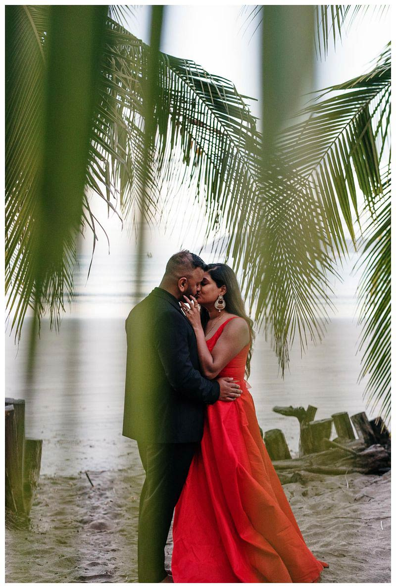 Couple kissing under palm trees on the beach in Costa Rica. Sunrise beach engagement photos in Tamarindo Costa Rica. Photographed by Kristen M. Brown, Samba to the Sea Photography.