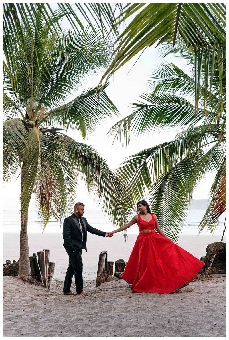 Couple dancing under palm trees on the beach in Costa Rica. Sunrise beach engagement photos in Tamarindo Costa Rica. Photographed by Kristen M. Brown, Samba to the Sea Photography.