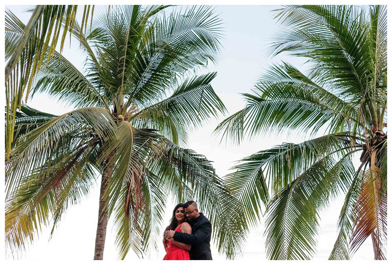 Couple hugging under palm trees on the beach in Costa Rica. Sunrise beach engagement photos in Tamarindo Costa Rica. Photographed by Kristen M. Brown, Samba to the Sea Photography.