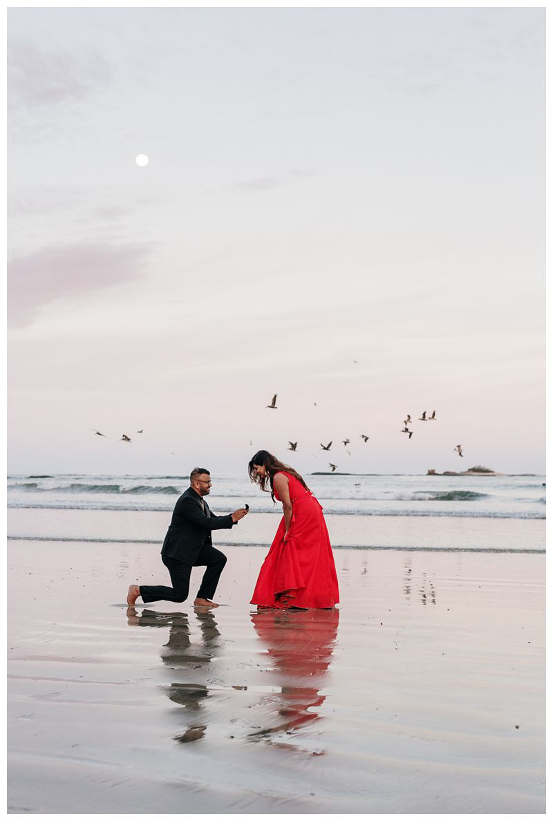 Boyfriend proposing to his girlfriend on the beach in Costa Rica. Sunrise beach engagement photos in Tamarindo Costa Rica. Photographed by Kristen M. Brown, Samba to the Sea Photography.