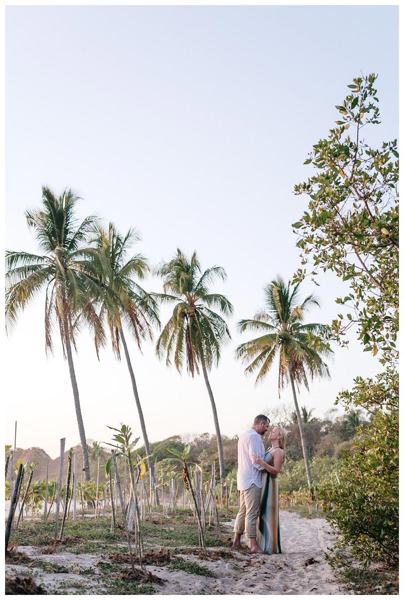 Couple kissing under palm trees on the beach in Noara. Playa Guiones Costa Rica engagement photos. Photographed by Kristen M. Brown, Samba to the Sea Photography.