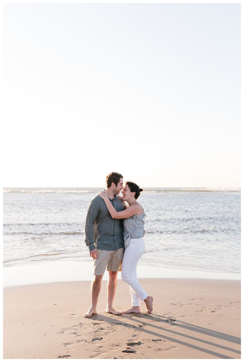 Couple laughing on the beach. Proposal on the beach in Tamarindo Costa Rica. Photographed by Kristen M. Brown, Samba to the Sea Photography.