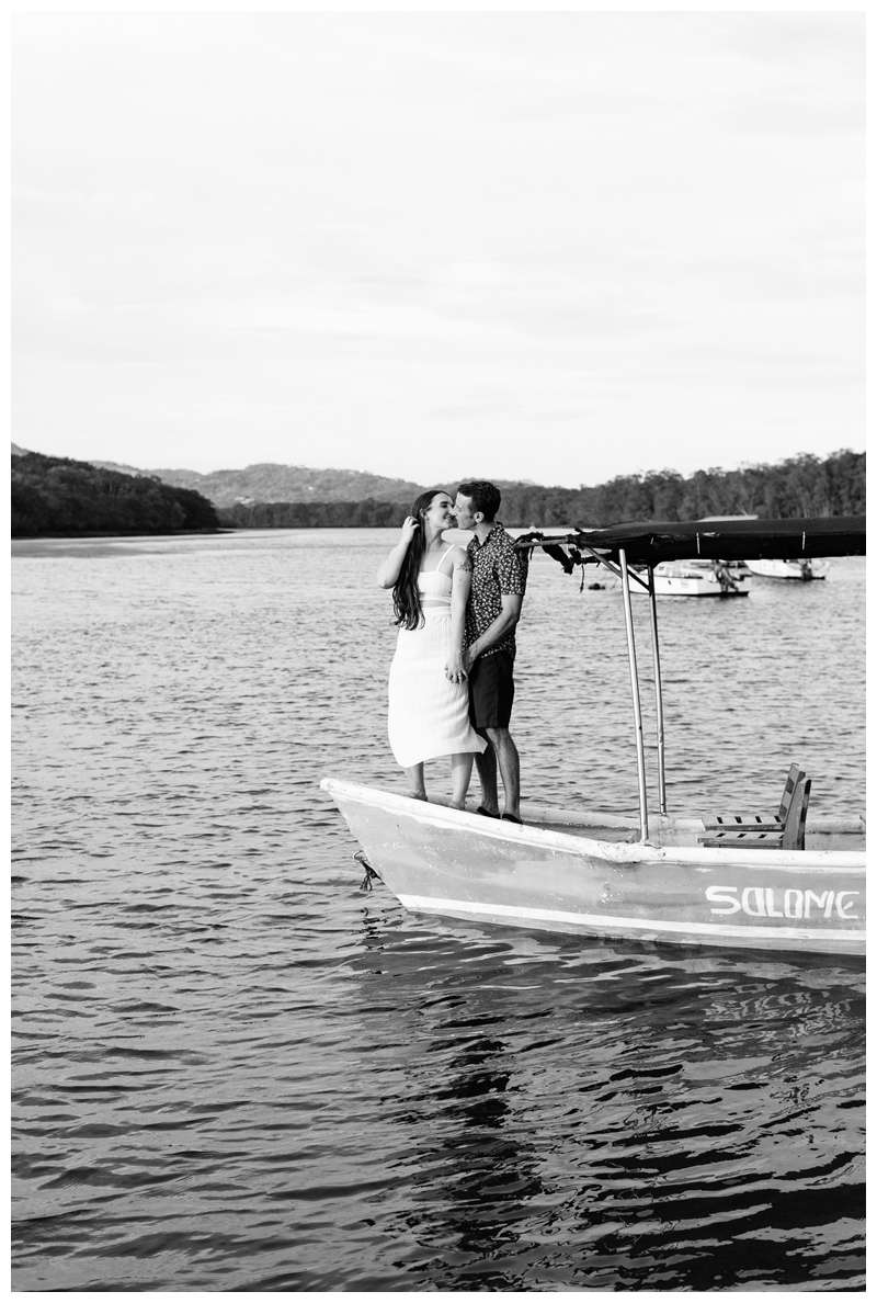 Couple on a Panga boat kissing. Engagement photos on the beach. Romantic proposal on the beach in Tamarindo Costa Rica. Photographed by Kristen M. Brown, Samba to the Sea Photography.