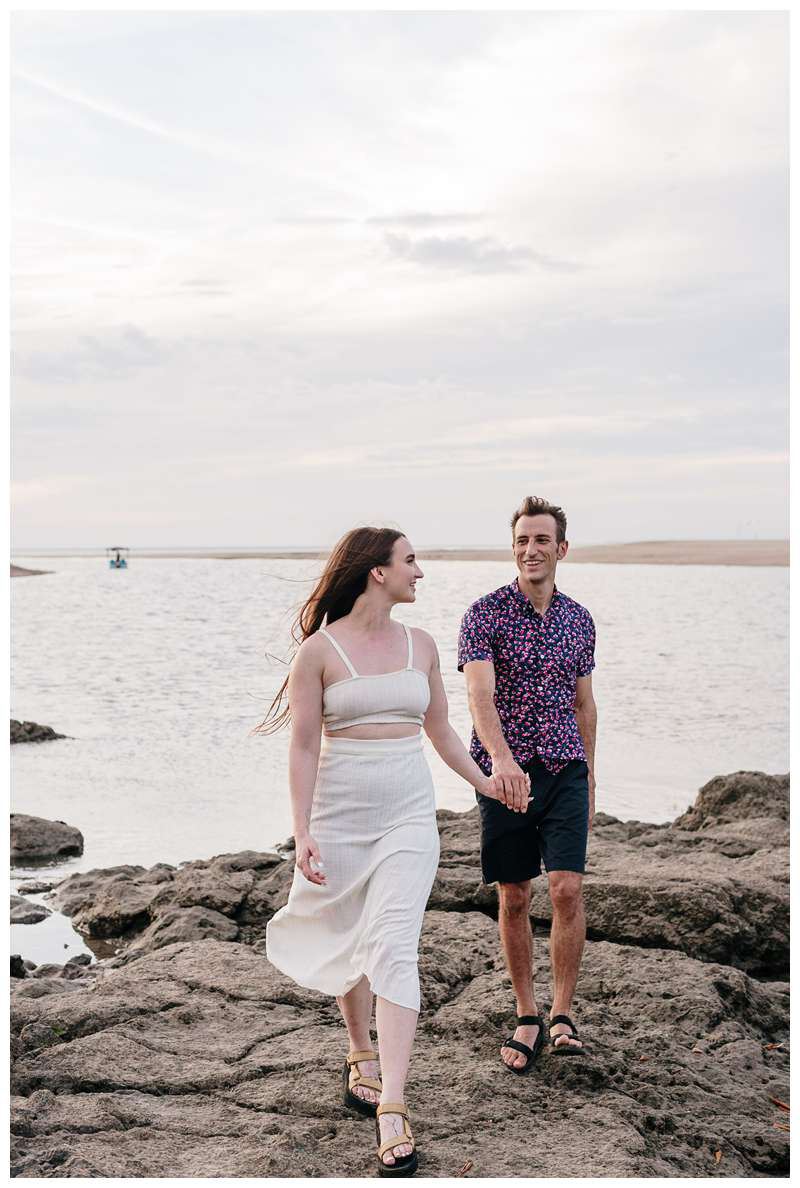 Couple walking during engagement photos on the beach. Romantic proposal on the beach in Tamarindo Costa Rica. Photographed by Kristen M. Brown, Samba to the Sea Photography.