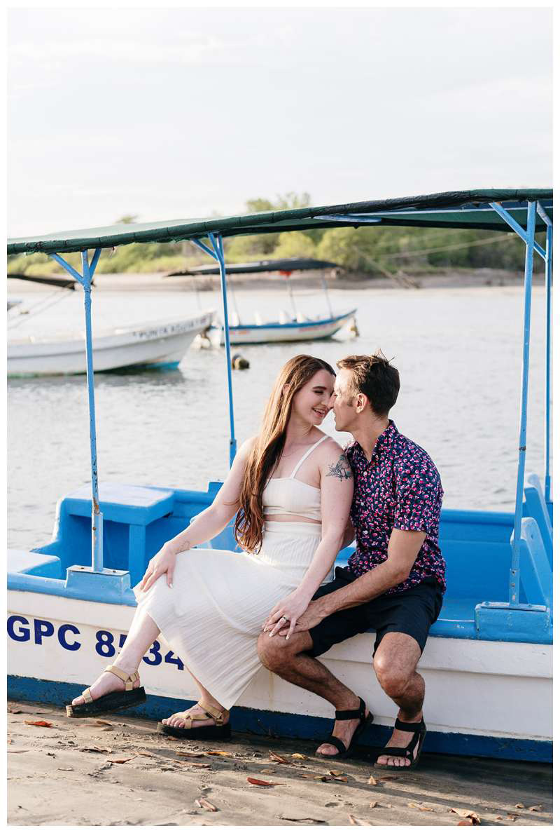 Couple sitting on a Panga boat kissing. Engagement photos on the beach. Romantic proposal on the beach in Tamarindo Costa Rica. Photographed by Kristen M. Brown, Samba to the Sea Photography.