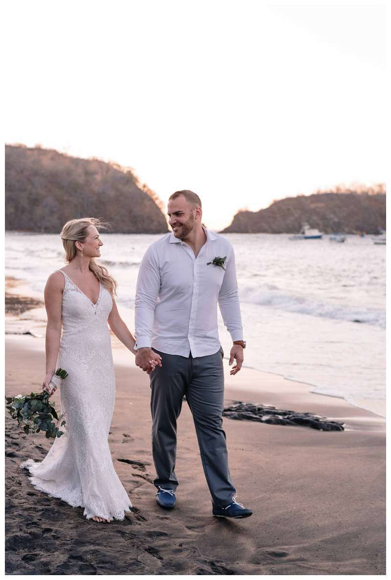 Bride and groom walking on the beach after their intimate wedding in Playa Ocotal Costa Rica. Photographed by Kristen M. Brown, Samba to the Sea Photography.
