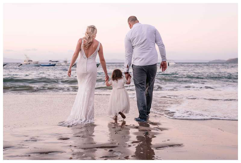Bride and groom walking on the beach with their little girl after their intimate wedding in Playa Ocotal Costa Rica. Photographed by Kristen M. Brown, Samba to the Sea Photography.