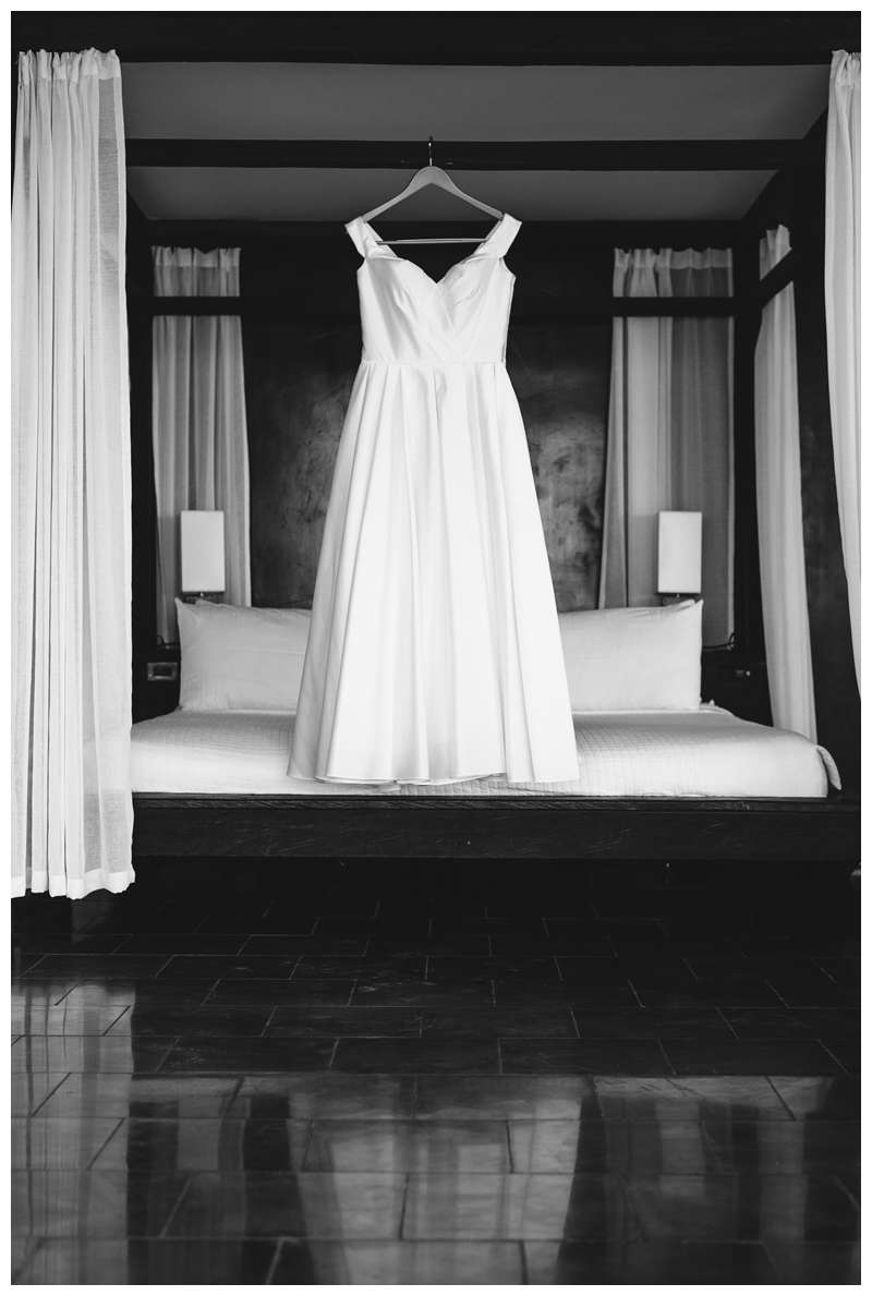 Wedding gown hanging on bed at intimate wedding in Tamarindo Costa Rica at Alang Alang. Photographed by Kristen M. Brown, Samba to the Sea Photography.