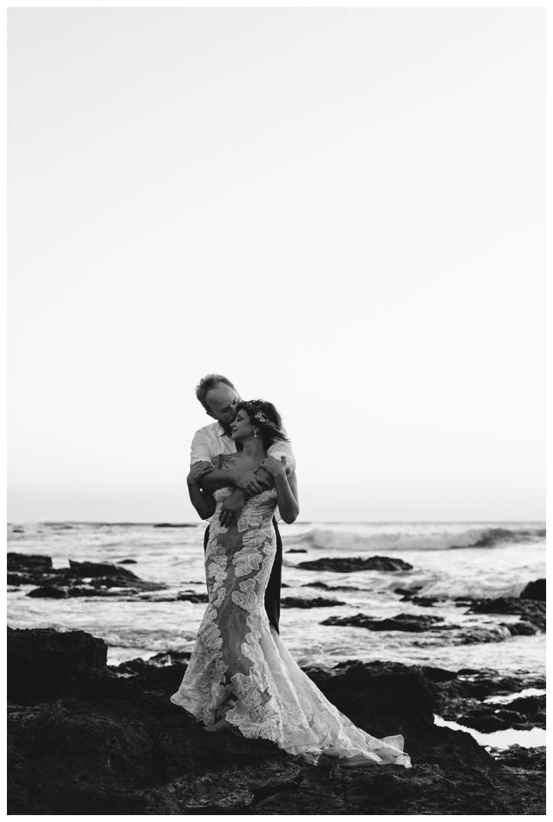 Couple standing on volcanic rocks after their vow renewal in Tamarindo Costa Rica. Photographed by Kristen M. Brown of Samba to the Sea Photography.