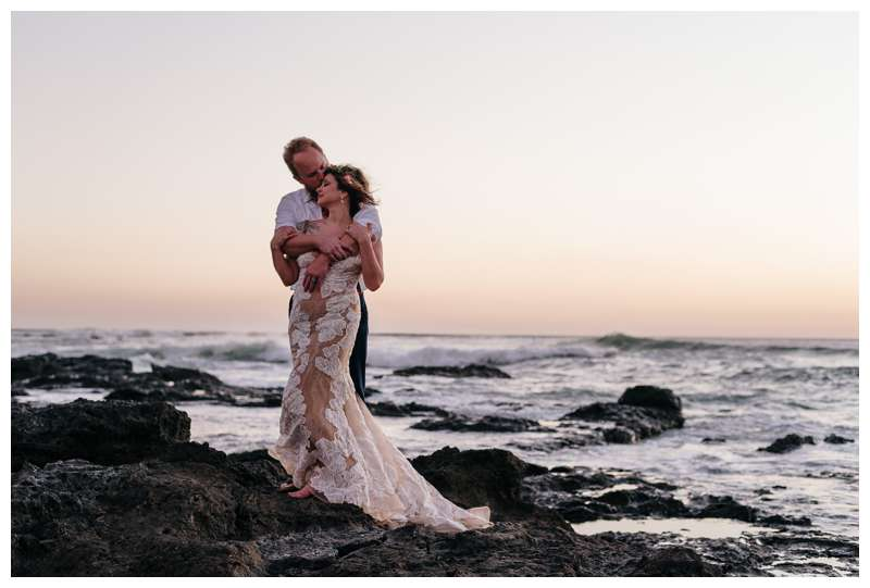 Couple standing on volcanic rocks during sunset after their vow renewal in Tamarindo Costa Rica. Photographed by Kristen M. Brown of Samba to the Sea Photography.