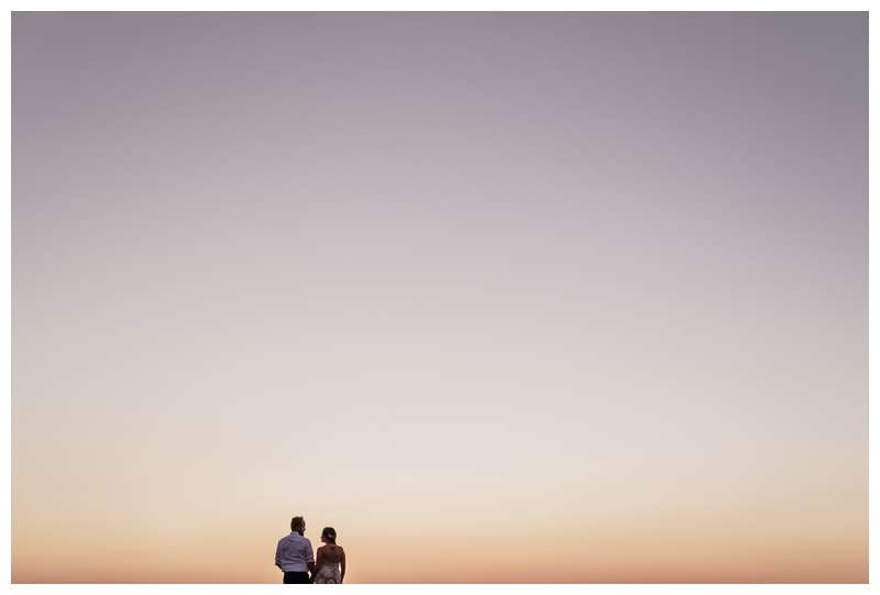 Couple watching sunset on the beach after their vow renewal in Tamarindo Costa Rica. Photographed by Kristen M. Brown of Samba to the Sea Photography.