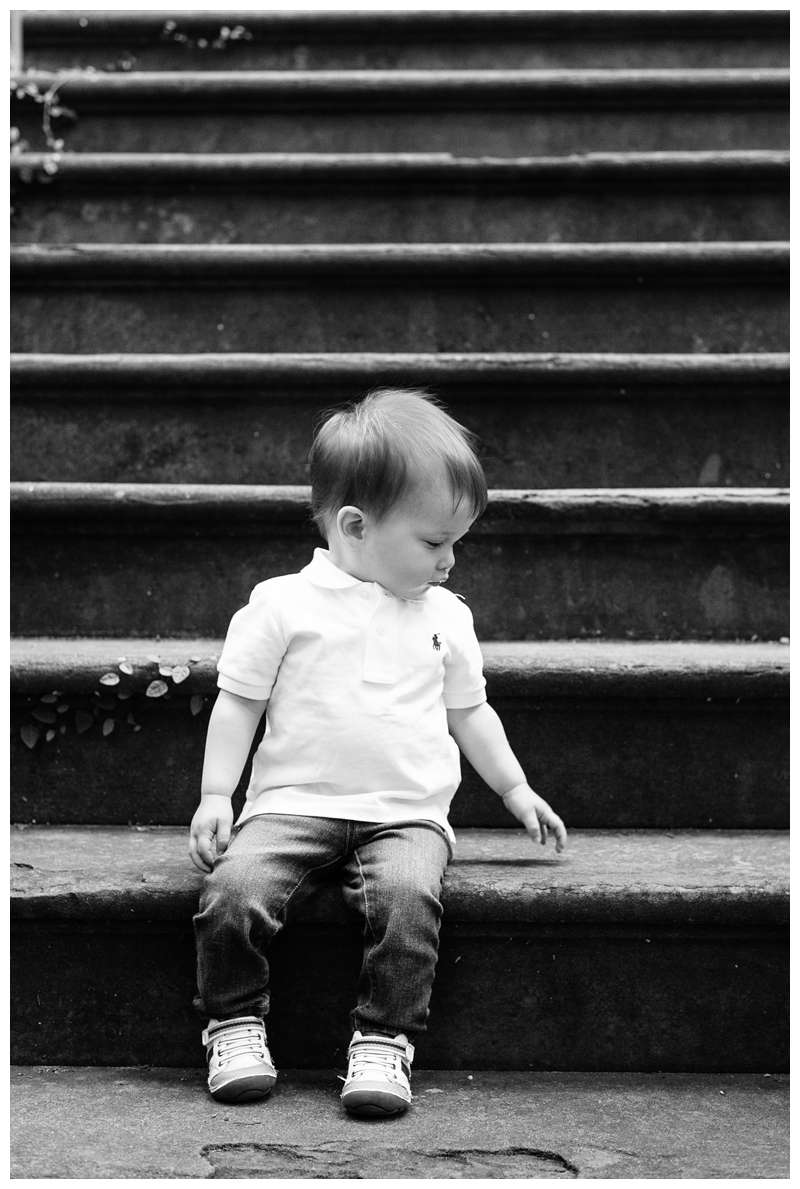 Little boy sitting on steps of Alex Raskins antiques. Downtown Savannah Georgia family photos photographed by Kristen M. Brown of Samba to the Sea Photography.