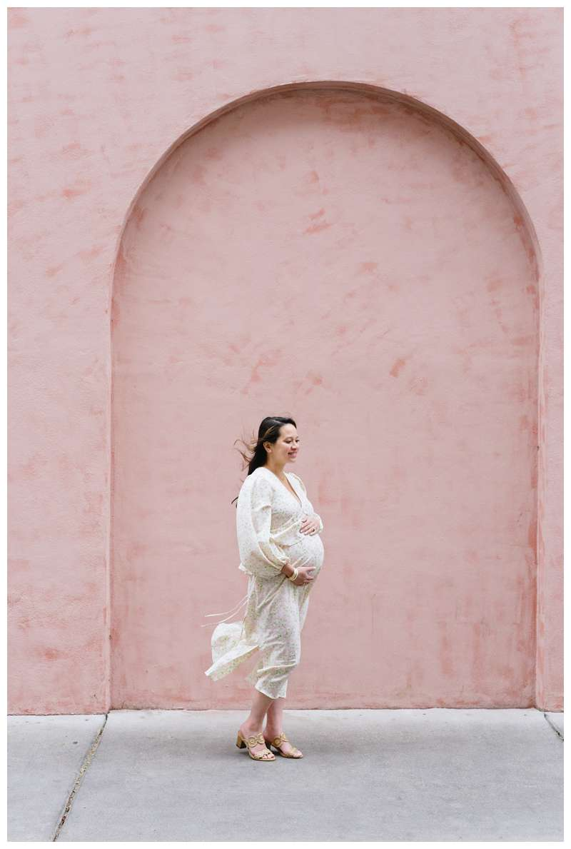 Pregnant woman in front of pink wall at Olde Pink House in Savannah. Downtown Savannah Georgia family photos photographed by Kristen M. Brown of Samba to the Sea Photography.