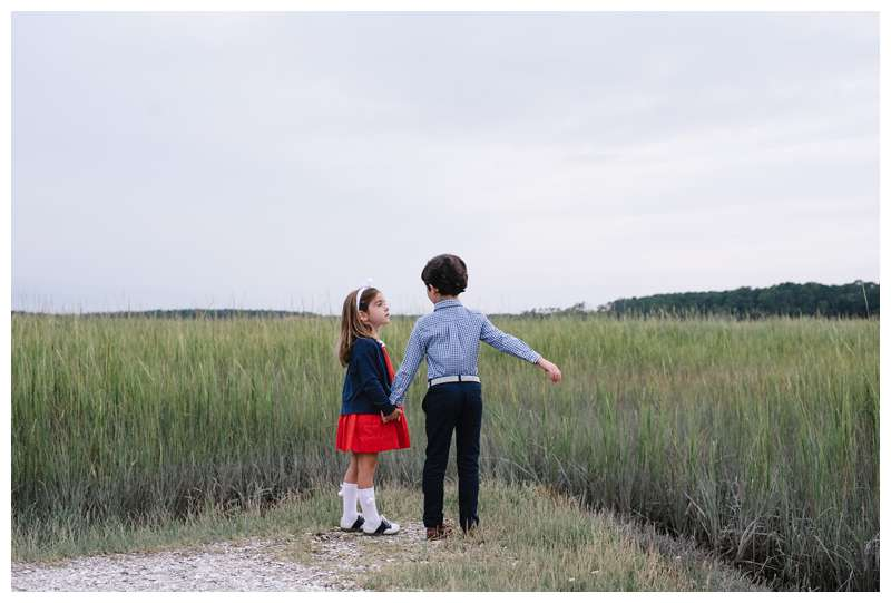 Siblings holding hands in front of the marsh. Fall family photos at The Landings in Savannah Georgia. Downtown Savannah Georgia family photos photographed by Kristen M. Brown of Samba to the Sea Photography.