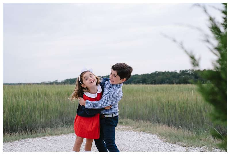 Siblings playing in front of the marsh. Fall family photos at The Landings in Savannah Georgia. Downtown Savannah Georgia family photos photographed by Kristen M. Brown of Samba to the Sea Photography.