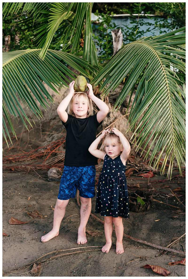 Little kids holding coconuts on their heads. Family vacation beach photos in Costa Rica. Photographed by Kristen M. Brown of Samba to the Sea Photography.