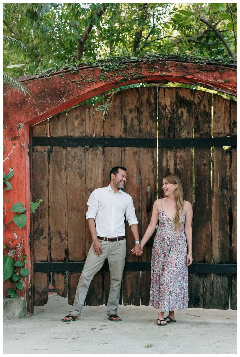 Couple standing in front of a wood door. Beach engagement photos in Playa Langosta, Costa Rica. Photographed by Kristen M. Brown of Samba to the Sea Photography.