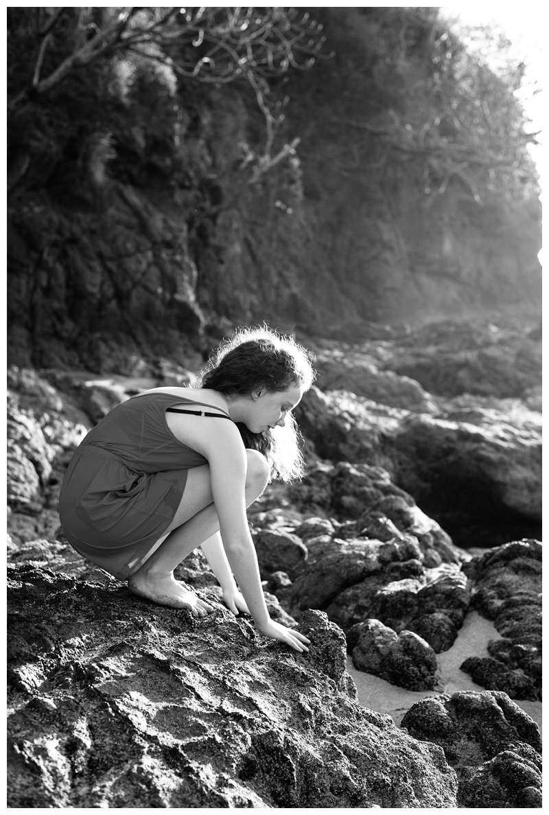 Girl playing on the low tide rocks during family Christmas vacation in Playa Potero Costa Rica family photos. Photographed by Kristen M. Brown of Samba to the Sea Photography.