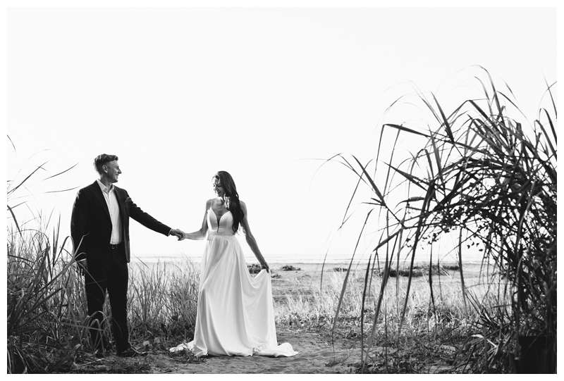 Bride and groom holding hands during sunset in Tamarindo. Honeymoon elopement in Costa Rica in Tamarindo. Photographed by Kristen M. Brown of Samba to the Sea Photography.