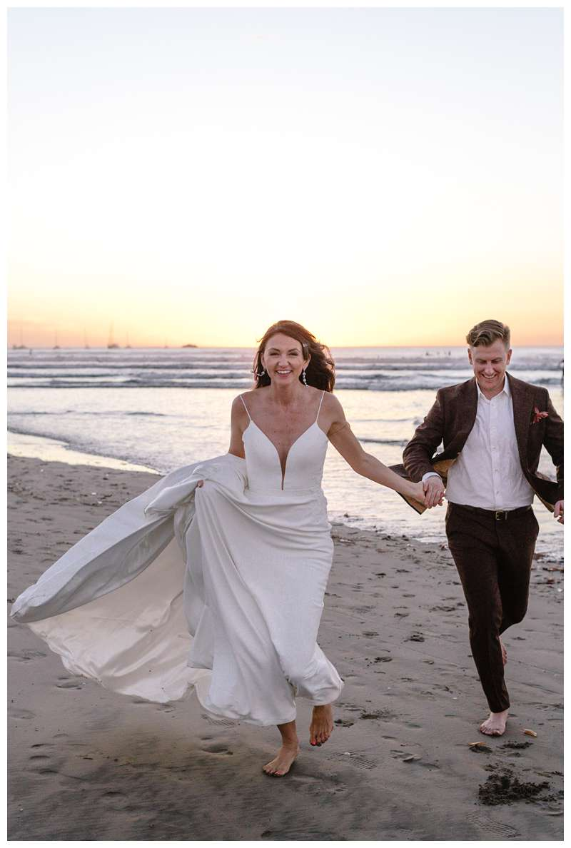 Bride and groom running on the beach during sunset in Tamarindo. Honeymoon elopement in Costa Rica in Tamarindo. Photographed by Kristen M. Brown of Samba to the Sea Photography.