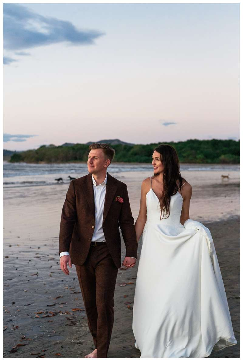 Bride and groom holding hands walking on the beach during sunset in Tamarindo. Honeymoon elopement in Costa Rica in Tamarindo. Photographed by Kristen M. Brown of Samba to the Sea Photography.