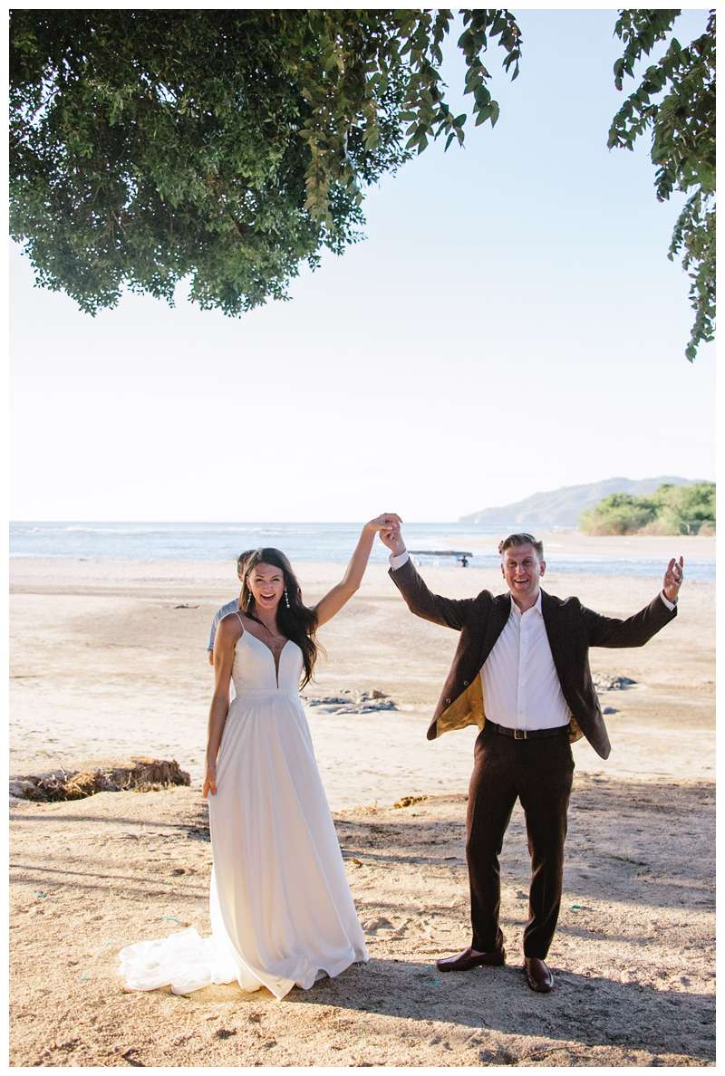 Bride and groom celebrating after their honeymoon elopement in Costa Rica in Tamarindo. Photographed by Kristen M. Brown of Samba to the Sea Photography.