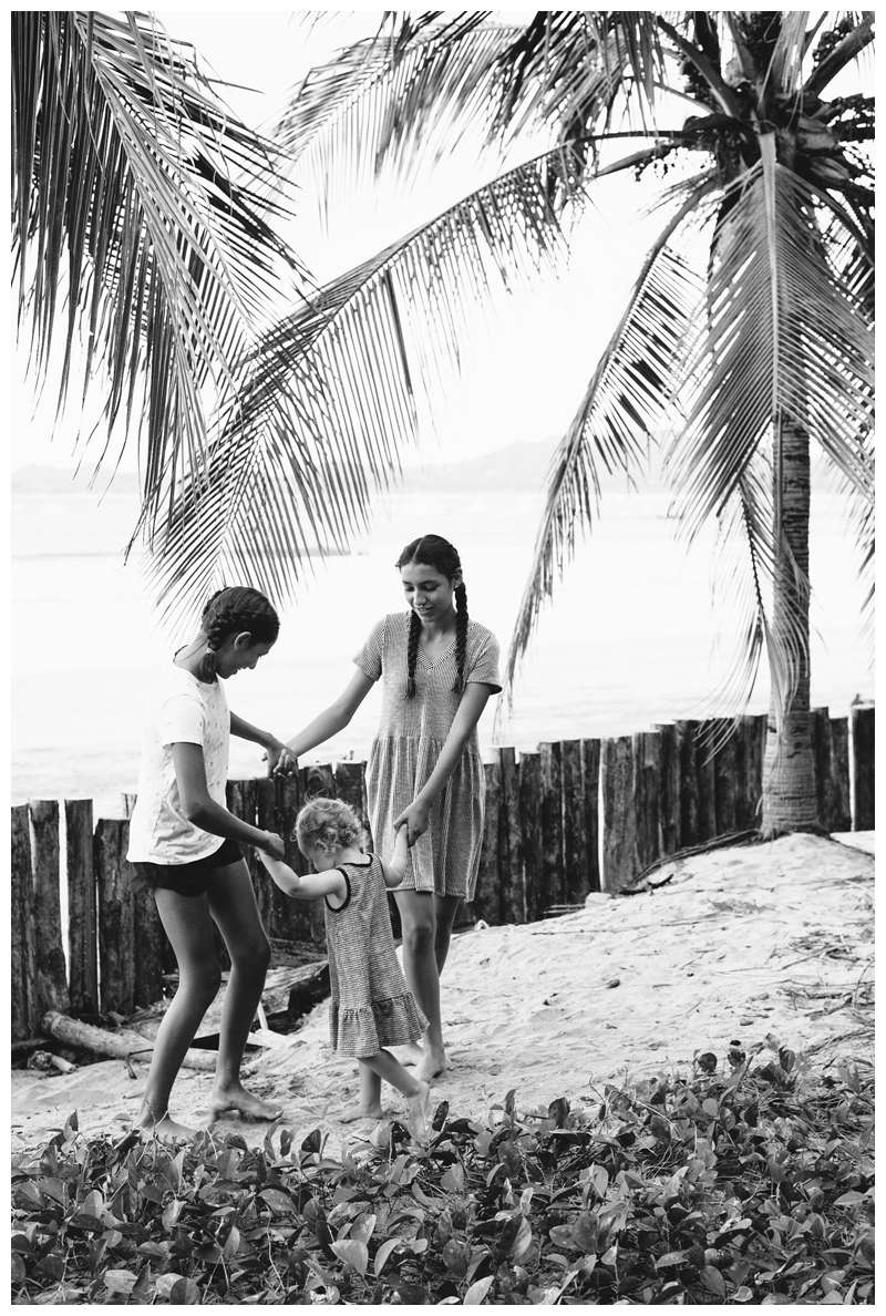 Sisters playing ring a round the rosy during family photos on the beach in Tamarindo Costa Rica. Photographed by Kristen M. Brown of Samba to the Sea Photography.
