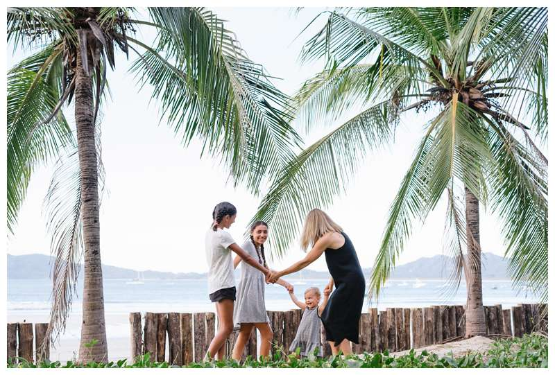Mom and her daughters playing ring a round the rosy during family photos on the beach in Tamarindo Costa Rica. Photographed by Kristen M. Brown of Samba to the Sea Photography.