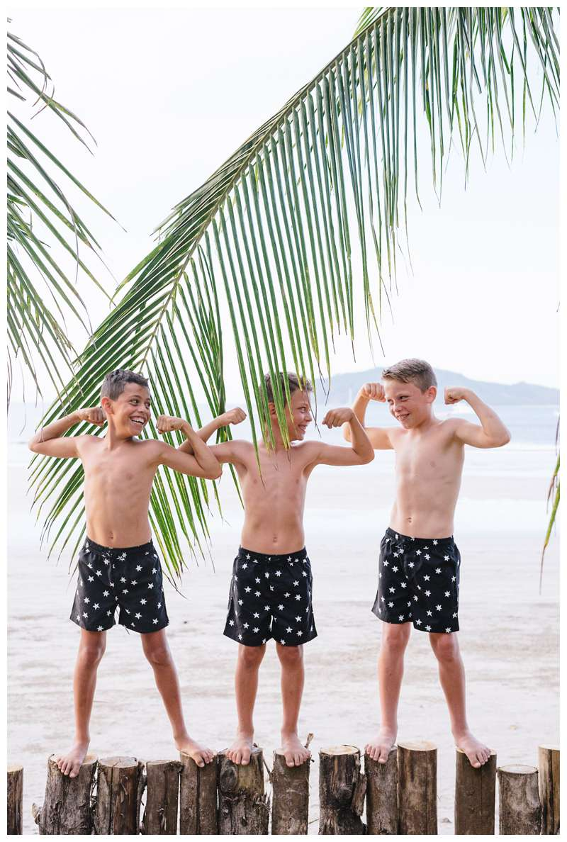 Brothers flexing their muscles during family photos on the beach in Tamarindo Costa Rica. Photographed by Kristen M. Brown of Samba to the Sea Photography.