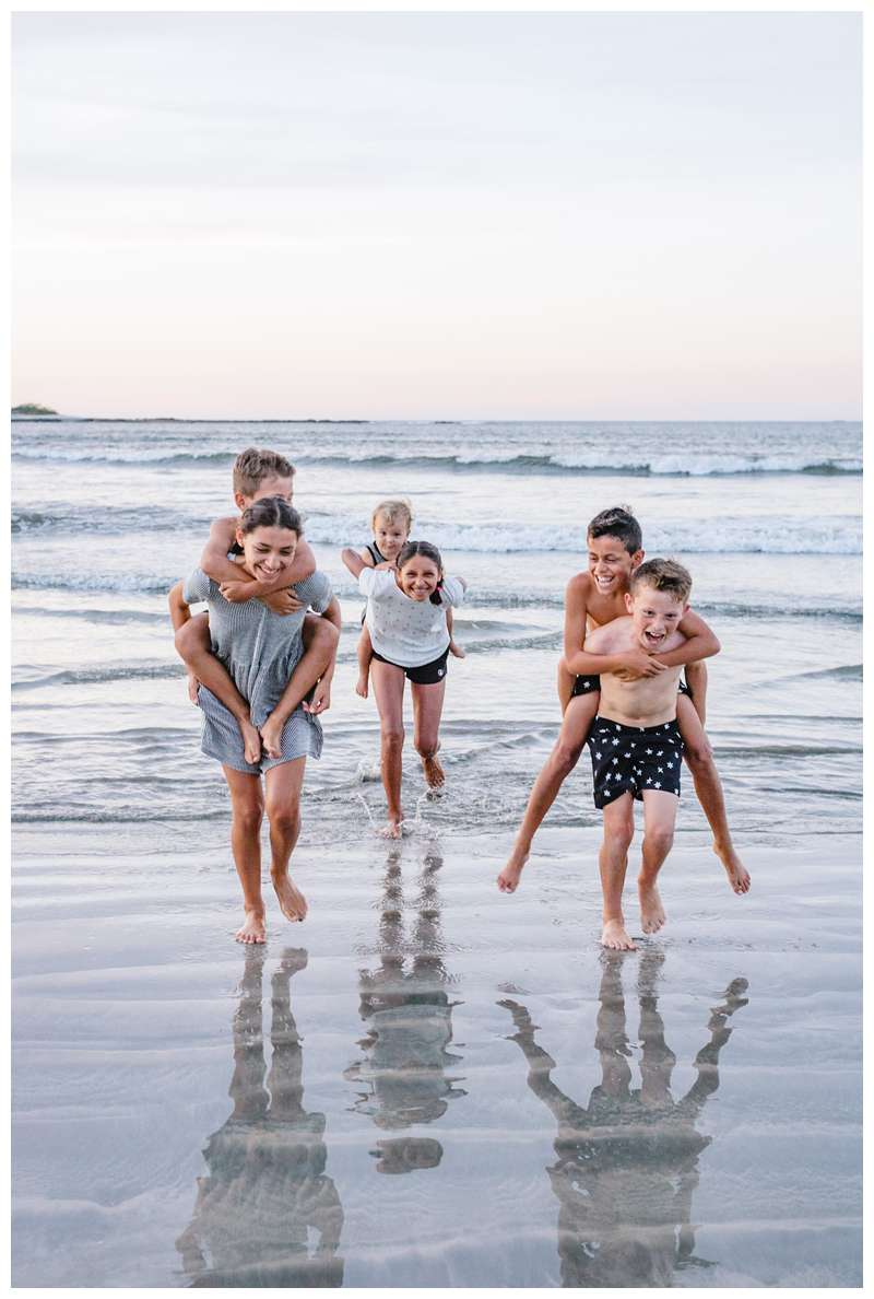Sibling running in the ocean during family photos on the beach in Tamarindo Costa Rica. Photographed by Kristen M. Brown of Samba to the Sea Photography.