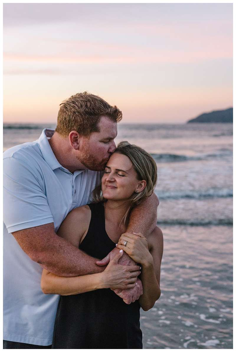 Mom and dad embracing during sunset family photos on the beach in Tamarindo Costa Rica. Photographed by Kristen M. Brown of Samba to the Sea Photography.