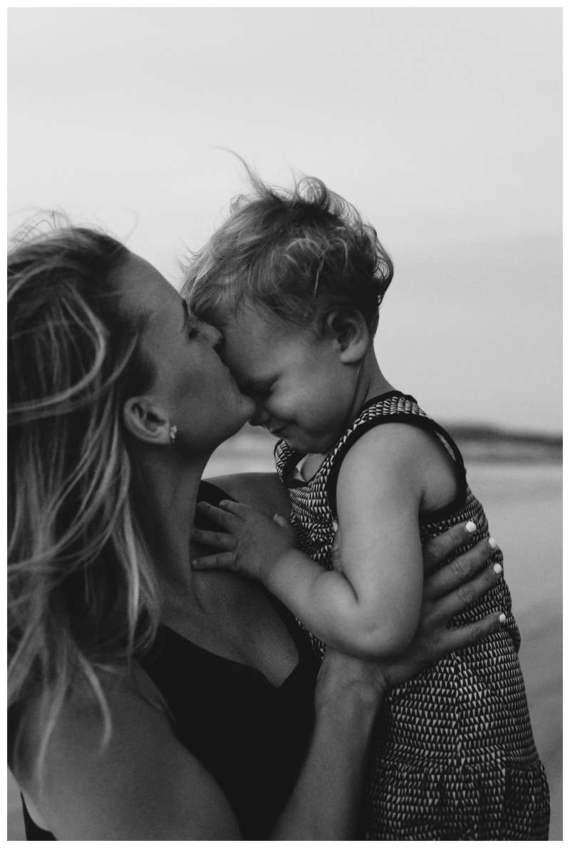 Mom kissing her little girl during family photos on the beach in Tamarindo Costa Rica. Photographed by Kristen M. Brown of Samba to the Sea Photography.
