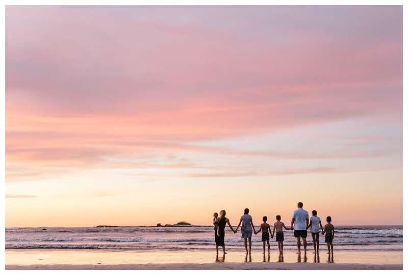 Family holding hands during sunset family photos on the beach in Tamarindo Costa Rica. Photographed by Kristen M. Brown of Samba to the Sea Photography.