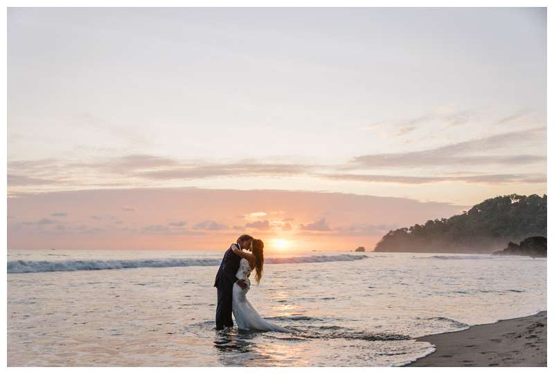 Bride and groom kissing on the beach during sunset after their destination wedding in Manuel Antonio Costa Rica at Villa Punto de Vista.