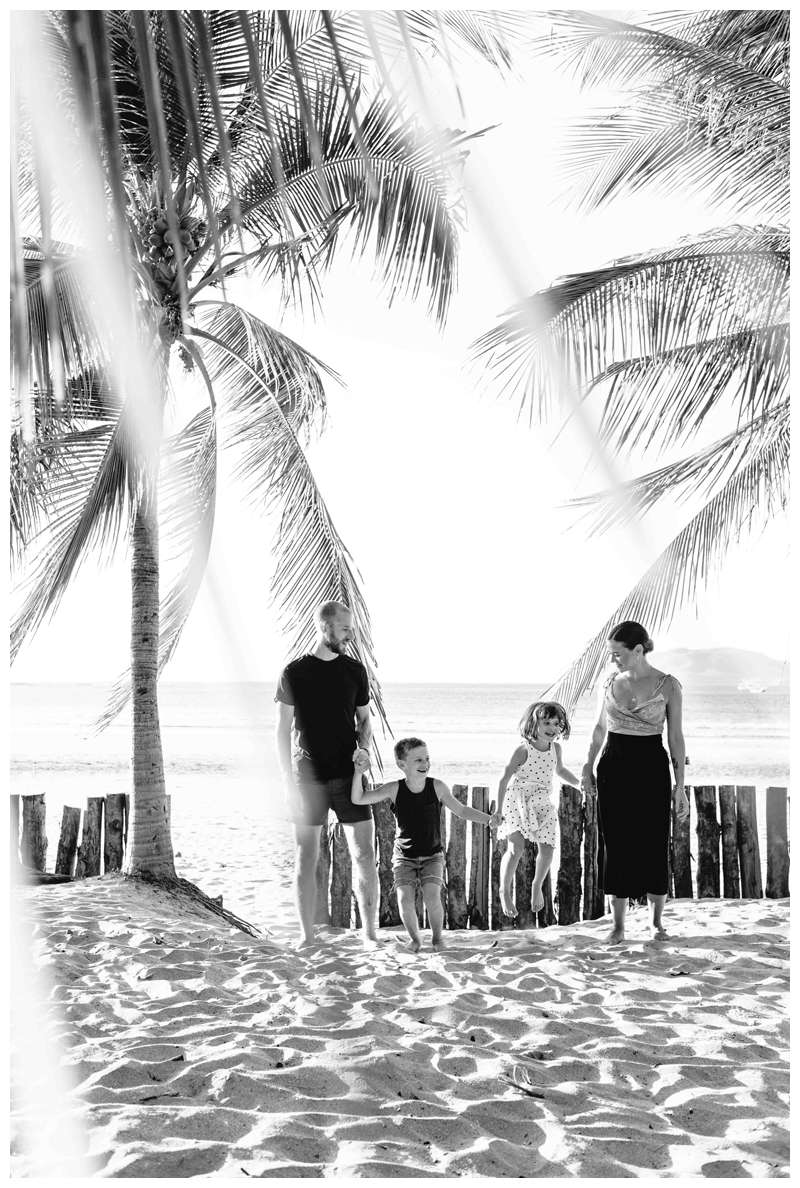 Family playing on the beach in Tamarindo underreported palm trees. Lifestyle family photos in Costa Rica. Photographed by Kristen M. Brown of Samba to the Sea.