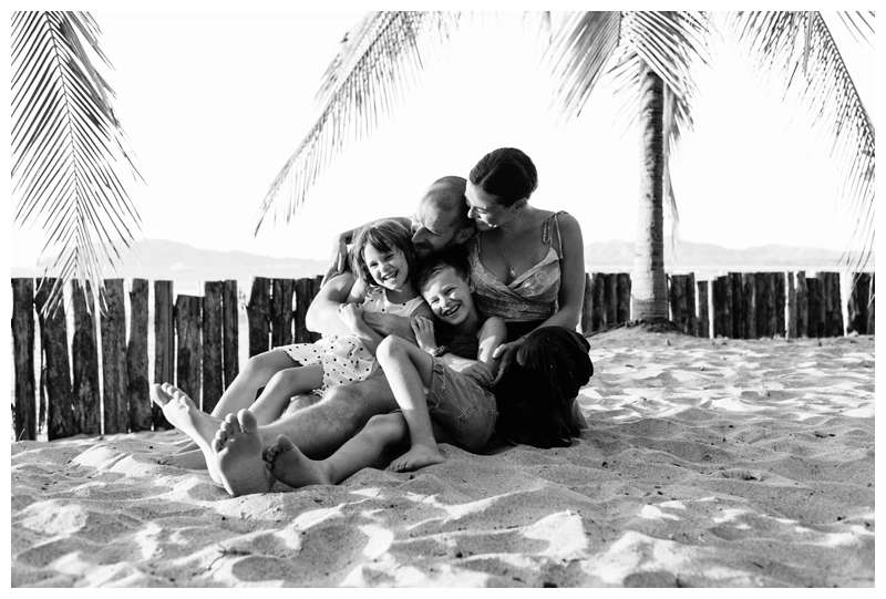 Family laughing on the beach in Tamarindo underreported palm trees. Lifestyle family photos in Costa Rica. Photographed by Kristen M. Brown of Samba to the Sea.