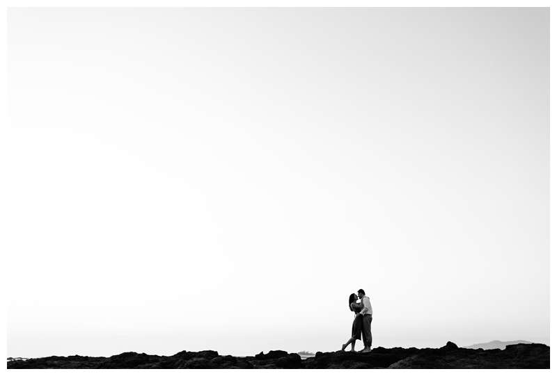 Black and white photo of couple kissing on the beach during for their engagement photos in Tamarindo Beach Costa Rica. Photographed by Kristen M. Brown of Samba to the Sea.