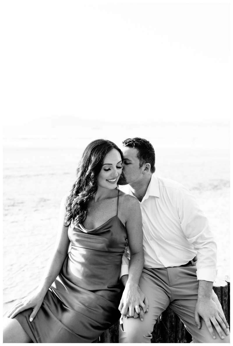 Black and white photo of couple kissing on the beach for their engagement photos in Tamarindo Beach Costa Rica. Photographed by Kristen M. Brown of Samba to the Sea.