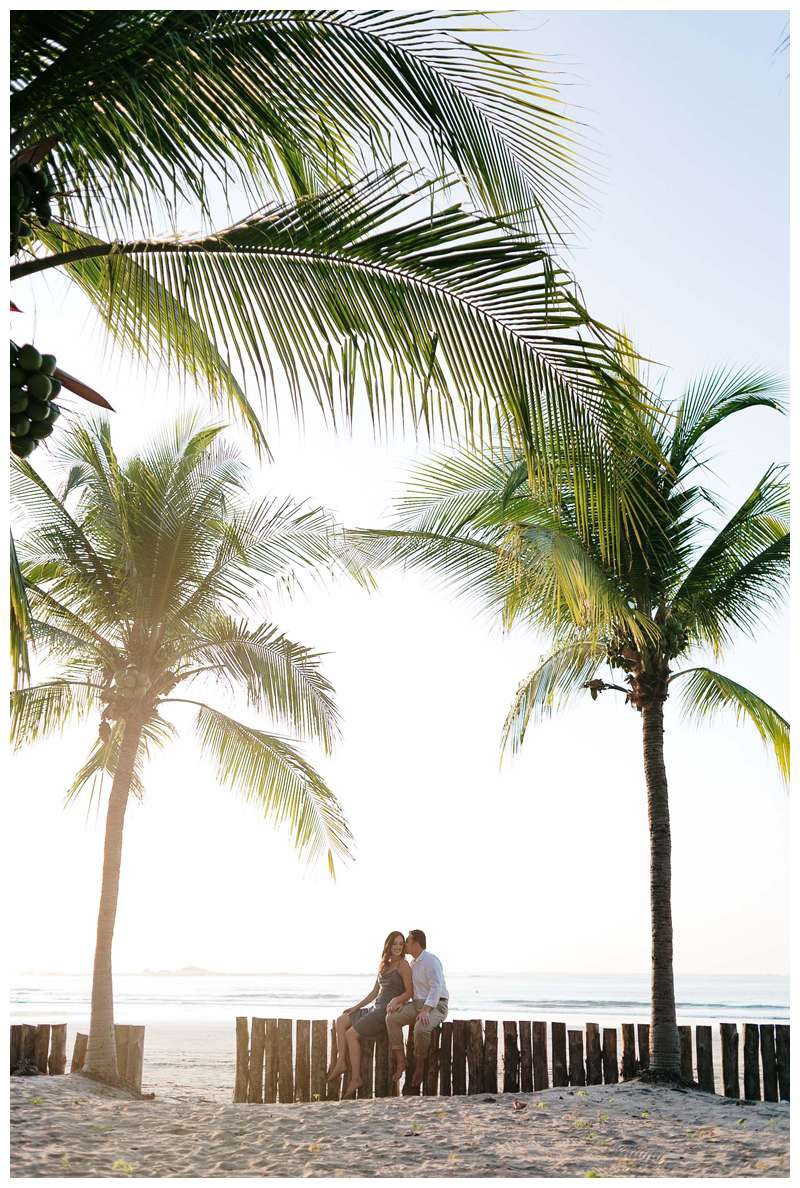 Couple kissing under palm trees on the beach for their engagement photos in Tamarindo Beach Costa Rica. Photographed by Kristen M. Brown of Samba to the Sea.
