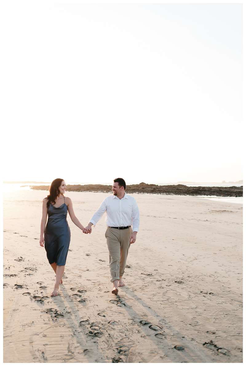 Couple walking on the beach for their engagement photos in Tamarindo Beach Costa Rica. Photographed by Kristen M. Brown of Samba to the Sea.