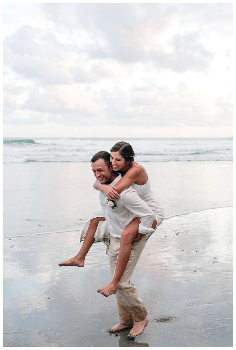 Groom giving his wife a piggy back ride on the beach after their intimate destination wedding in Manuel Antonio Costa Rica at Casa Diamante.