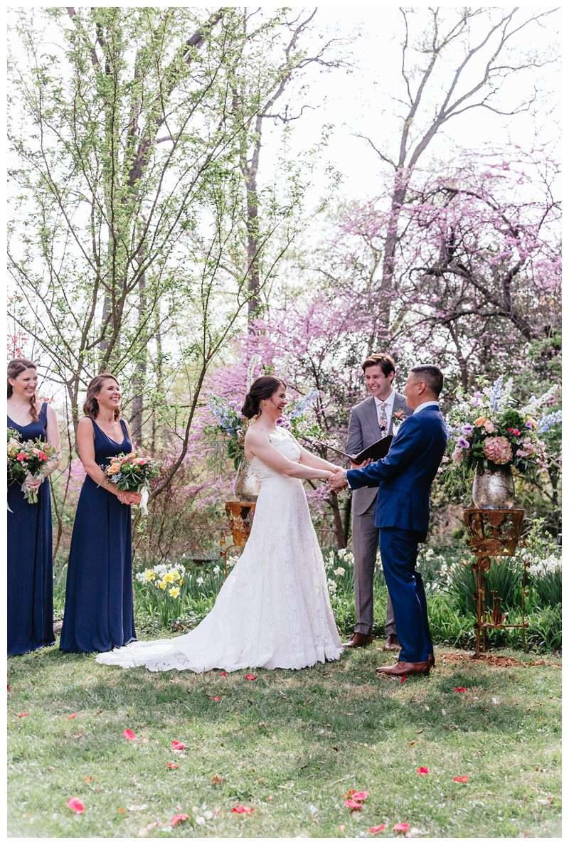 Bride and groom holding in the beautiful church gardens during their ceremony for their intimate historic Alexandria Virgina spring wedding. Photographed by Kristen M. Brown of Samba to the Sea.